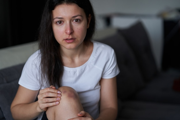 Portrait of beaten woman with tears of her face and bruise on knee sit on the sofa.