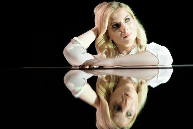 Portrait of a beautiful actress near a white piano.