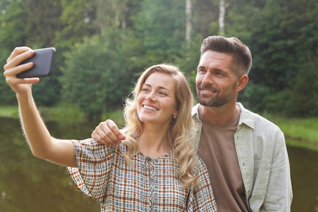 Portrait of beautiful adult couple taking selfie while posing by lake in green countryside scenery