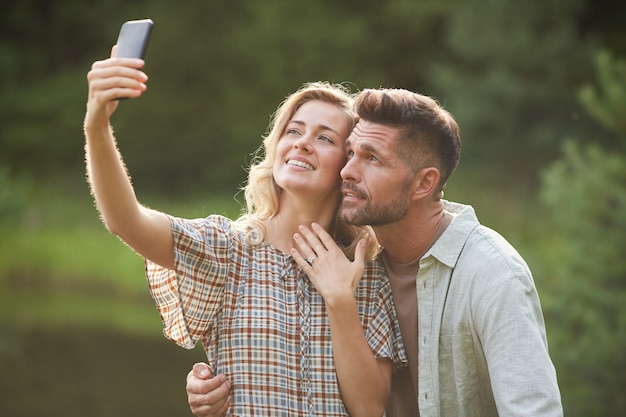 Portrait of beautiful adult couple taking selfie with engagement ring after marriage proposal during romantic date outdoors