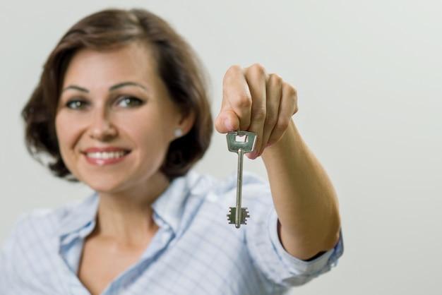 Portrait of beautiful adult woman holding key