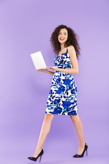 Portrait of beautiful adult woman with curly hair in dress smiling and walking with laptop in hands