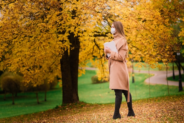 Portrait of a beautiful adult young woman on the background of autumn in park in medical face mask