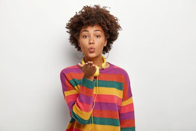 Il ritratto di una bella ragazza adolescente riccia e affettuosa tiene i palmi allungati in avanti, le labbra arrotondate, manda un bacio d'aria, indossa un maglione colorato casual, usa le cuffie per ascoltare le melodie preferite