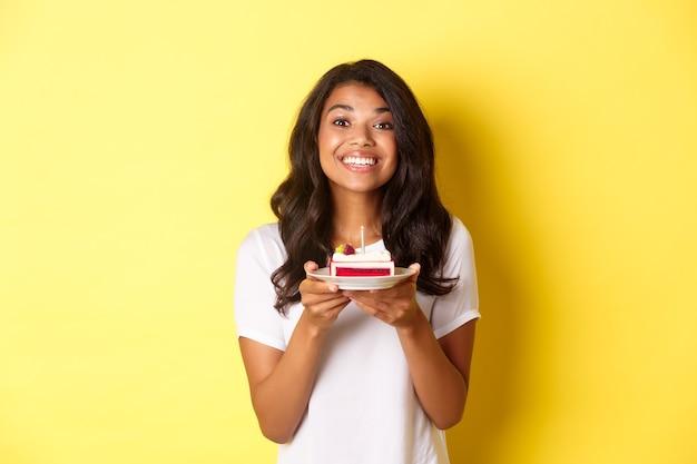 Ritratto di bella ragazza afro-americana che festeggia il compleanno, sorride e sembra felice e tiene in mano una torta di compleanno con una candela, in piedi su sfondo giallo