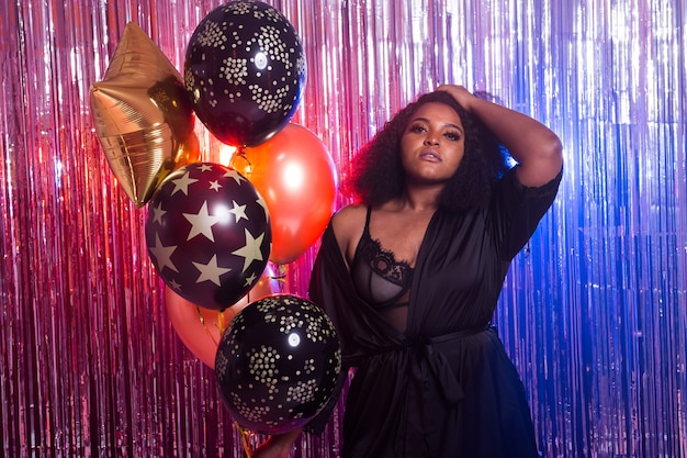 Portrait of a beautiful african american woman against twinkling background. birthday party