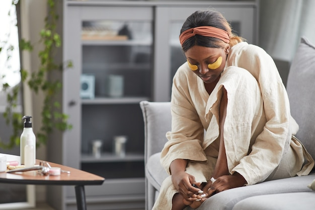 Portrait of beautiful african-american woman enjoying skincare routine at home and doing pedicure, copy space