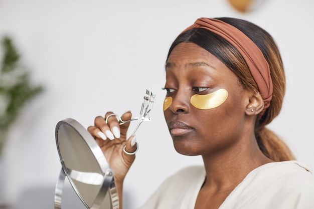 Portrait of beautiful african-american woman enjoying skincare routine at home and holding mirror, copy space