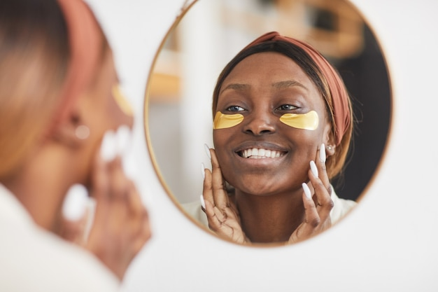 Portrait of beautiful african-american woman enjoying skincare routine at home and looking at mirror, copy space