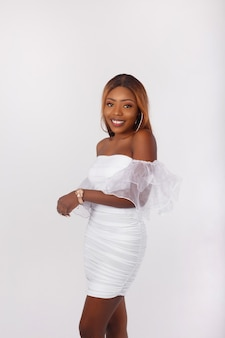 Portrait of a beautiful african american woman in short white dress smiling on white background