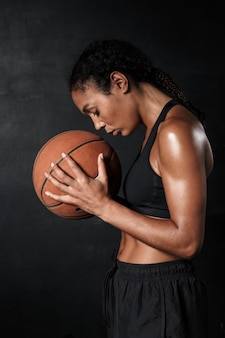 Portrait of beautiful african american woman in sportswear holding basketball isolated on black