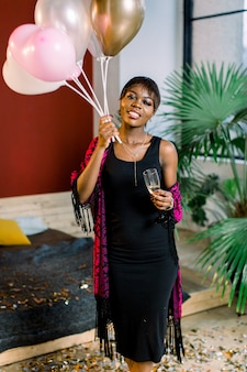 Portrait of beautiful african girl resting at birthday party with balloons and a glass of champagne in her hands