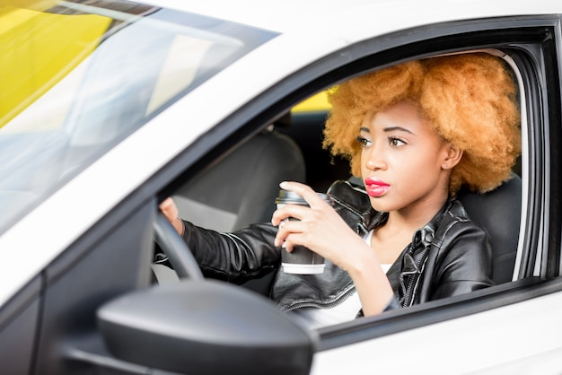 Portrait of a beautiful african woman in leather jacket with coffee cup sitting in the car on the yellow background
