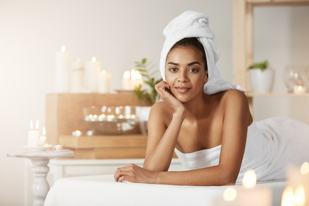 Portrait of beautiful african woman with towel on head smiling resting in spa salon.