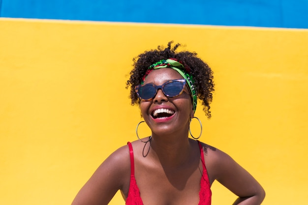 Portrait of beautiful afro american woman hands on face while smiling