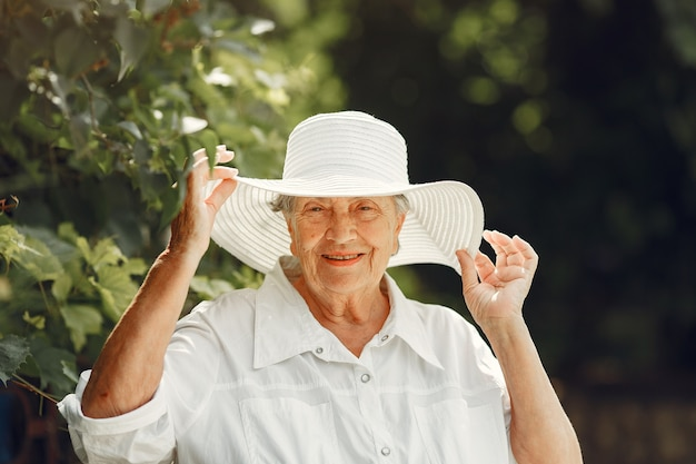 Portrait of beautiful aged woman in the park. grandma in a white hat.