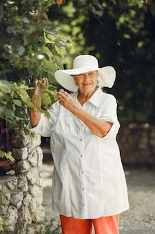Ritratto di bella donna invecchiata nel parco. nonna con un cappello bianco.