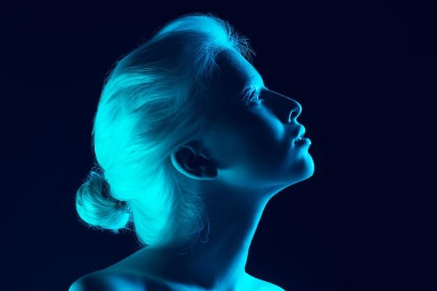 Portrait of beautiful albino girl isolated on dark studio background in neon light