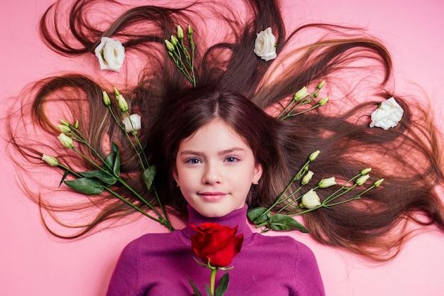 花の香水、ロマンチックな優しさと思春期の新鮮さの10代の無垢の吹き飛ばされていない芽を持つ肖像画の美しく魅力的な少女。赤いバラのバレンタインデーを保持している若い女性。
