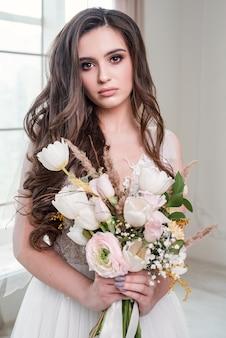 Портрет красивой и нежной молодой невесты в свадебном платье на свадебной фотосессии в фотостудии