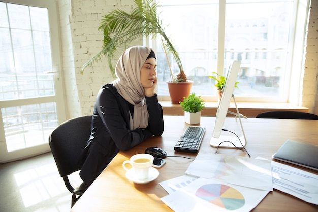 Portrait of a beautiful arabian businesswoman wearing hijab while working at openspace or office. concept of occupation, freedom in business area, leadership, success, modern solution.