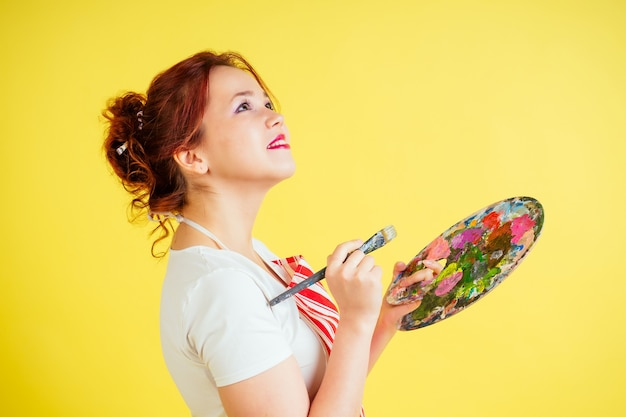 Portrait of a beautiful artist in an apron holding a palette and brush on a yellow background in the studio . inspiration and muse idea.