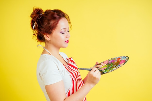 Portrait of a beautiful artist in an apron holding a palette and brush on a yellow background in the studio
