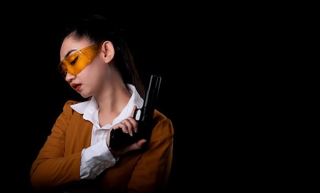黒の表面にピストル銃を保持している黄色のスーツ片手で身に着けている美しい海の女性の肖像画、カメラで拳銃を放つ若いセクシーな女の子の長い髪、ピストルできれいな女性が立っています。