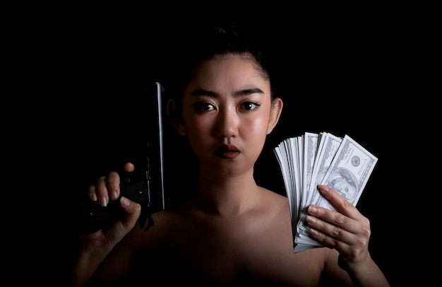 Portrait beautiful asia woman one hand holding a gun and money banknote 100 usd at black background, young sexy girl long hair with a handgun, pretty women stand with a pistol, look at the camera