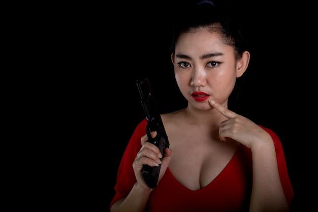 빨간 드레스를 입고 한 손에 권총 총 11mm를 들고 초상화 아름 다운 아시아 여자