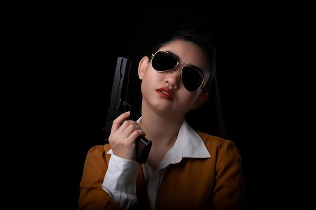 노란색 양복을 입고 한 손으로 권총 총을 들고 초상화 아름다운 아시아 여자