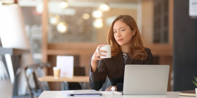 Portrait of beautiful asian businesswoman drinking coffee while working on her project with laptop computer