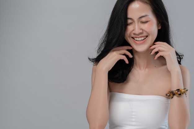 Portrait of beautiful asian girl with an evening make-up, model smiling on gray
