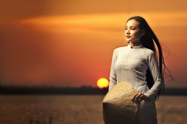Portrait of beautiful asian girls with ao dai vietnam traditional dress on sunset landscapes.