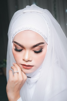 Portrait of a beautiful asian muslim bride with make up in white wedding dress and hijab headscarf