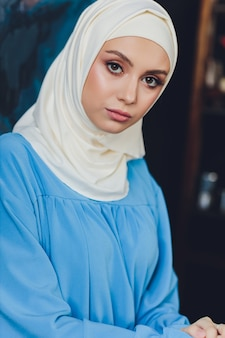 Portrait of a beautiful asian muslim woman model wearing white blouse and blue hijab posing on white curtain as background in close-up view