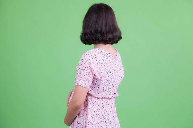 Portrait of beautiful asian pregnant woman with short hair against chroma key or green wall
