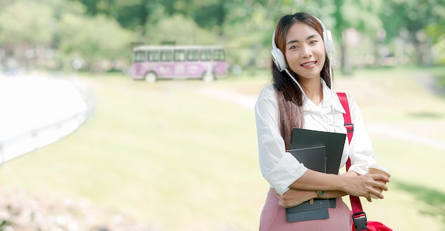 Portrait of beautiful asian university student with headphone and red sling bag holding book and coffee cup while standing outdoors.