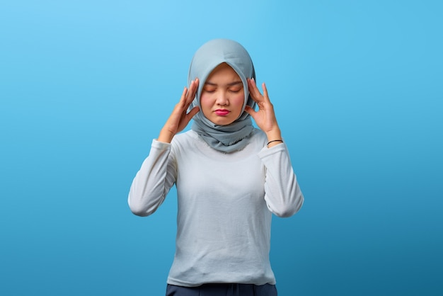 Portrait of beautiful asian woman feeling confused and headache on blue background