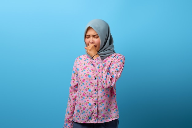 Portrait of beautiful asian woman feeling unwell and coughing on blue background