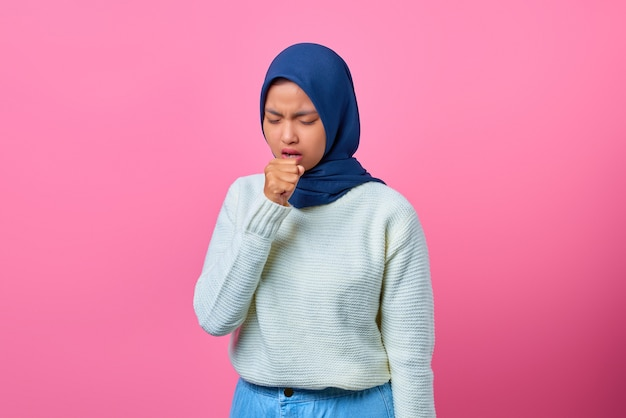 Portrait of beautiful asian woman feeling unwell and coughing on pink background