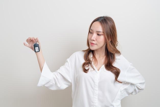 흰색 바탕에 자동차 키를 들고 초상화 아름 다운 아시아 여자
