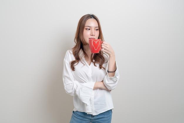 Портрет красивой азиатской женщины, держащей чашку кофе или кружку на белом фоне