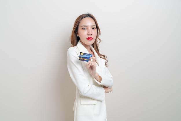 Портрет красивой азиатской женщины, держащей кредитную карту на белом фоне