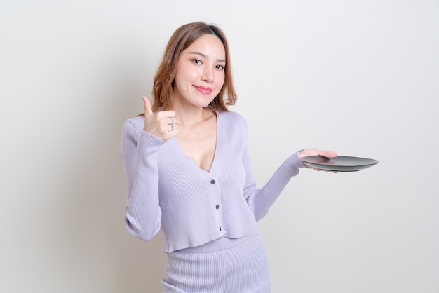 Portrait beautiful asian woman holding empty plate on white background