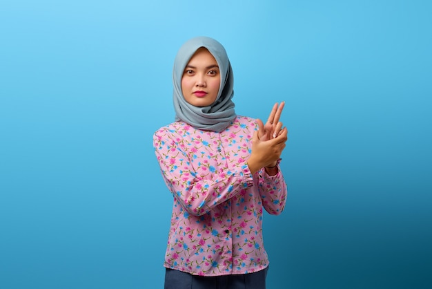 Portrait of beautiful asian woman holding symbolic gun with hand gesture