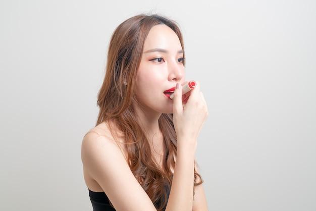白い背景の上の赤い口紅を構成し、使用している肖像画の美しいアジアの女性