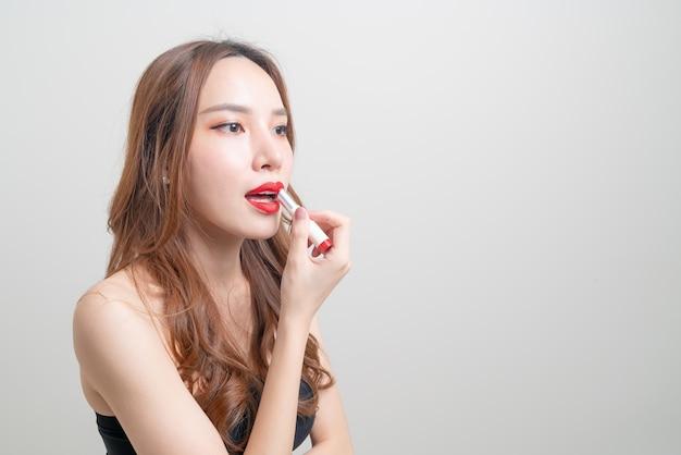 肖像画美しいアジアの女性が白い背景に赤い口紅を作り、使用しています