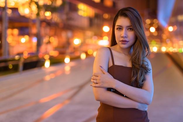 Portrait of beautiful asian woman outdoors in bangkok, thailand at night