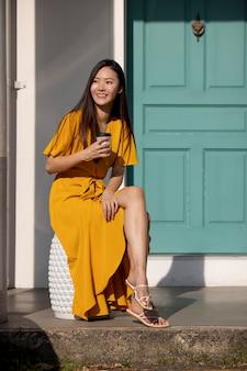 Ritratto di bella donna asiatica in posa all'aperto in città mentre beve caffè